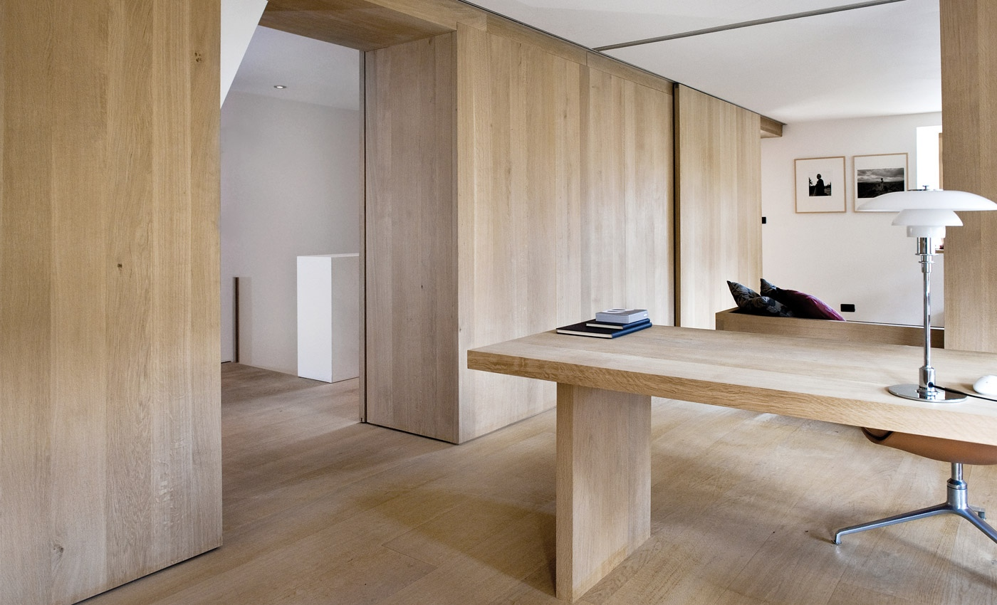 By creating walls and even a desk that match the wood flooring