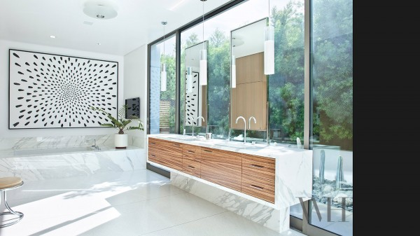 A modern bathroom have windows as wall as well, but still manages plenty of mirrors.