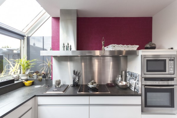 And bright burgundy accent wall makes this French kitchen feel more than welcoming.