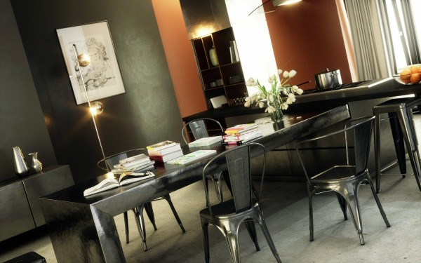The metal chairs and hammered metal table give this dining room a distinctly warm industrial feel.