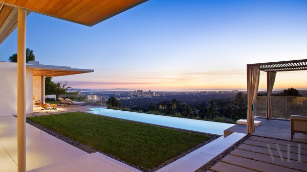 An infinity pool adds a serene glamour to the outdoor space while there is just enough grass for feeling it between your toes - even during a drought.