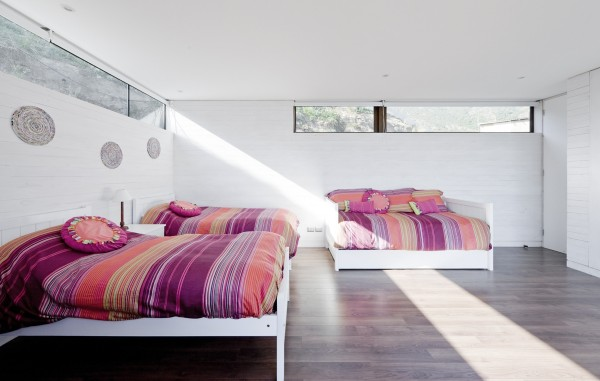 Adding splashes of color in the duvets here makes it easy to swap out, change, or bring back to white at any time.