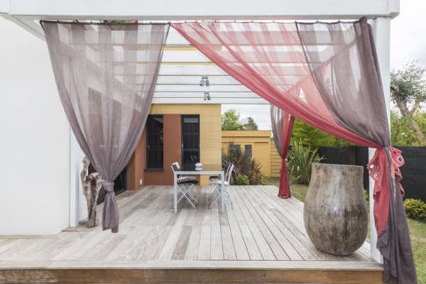 Gauzy curtains let you feign privacy for outdoor dinner parties.
