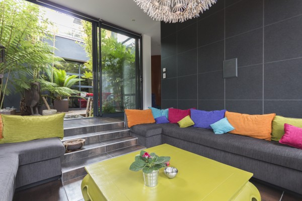 The use of colorful pillows breaks up the otherwise monotonous fade from dark gray walls to gray sofa to dark tiled floor.