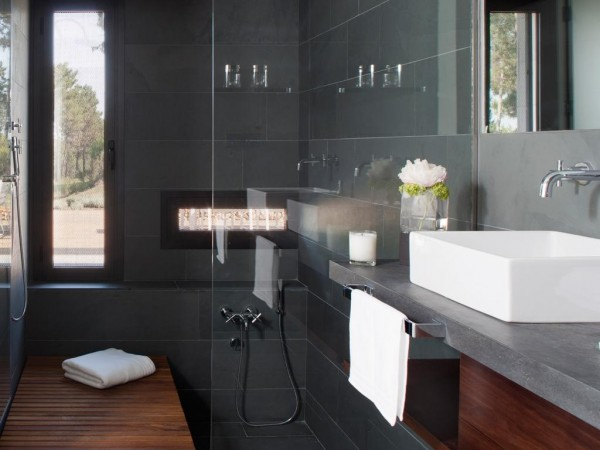 The bathrooms have their own careful luxury with this dark gray slate tile.