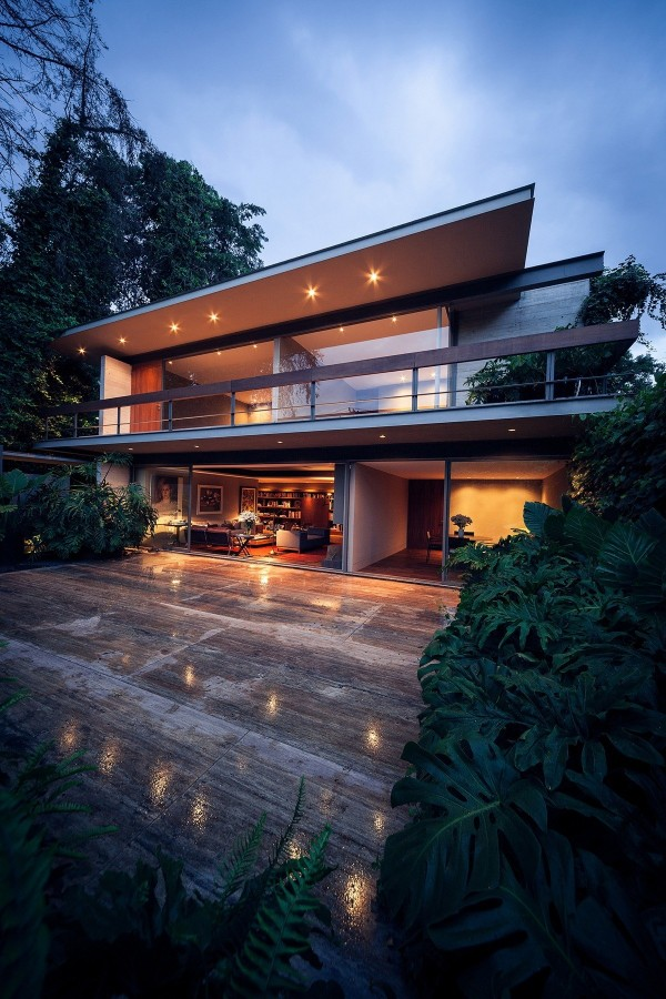 Lights from the overhang illuminate both the wraparound balcony and the stone patio below.