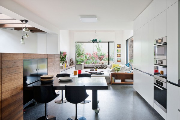 A modern kitchen, complete with a hightop breakfast table and dark, natural wood accents is sleek and simple.