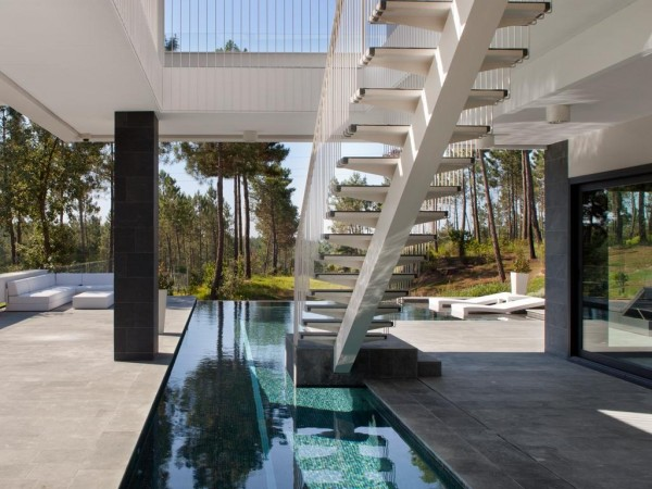 A modern staircase floats down from main house to the extensive pool deck.