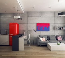 The open design here allows the color scheme from the kitchen - grey concrete with pops of red - to spill over into the living room, making the whole space feel unified.