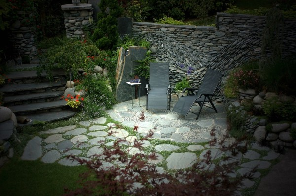 In this secluded patio, the stone mosaic background almost creates a static waterfall effect, but with more permanence.