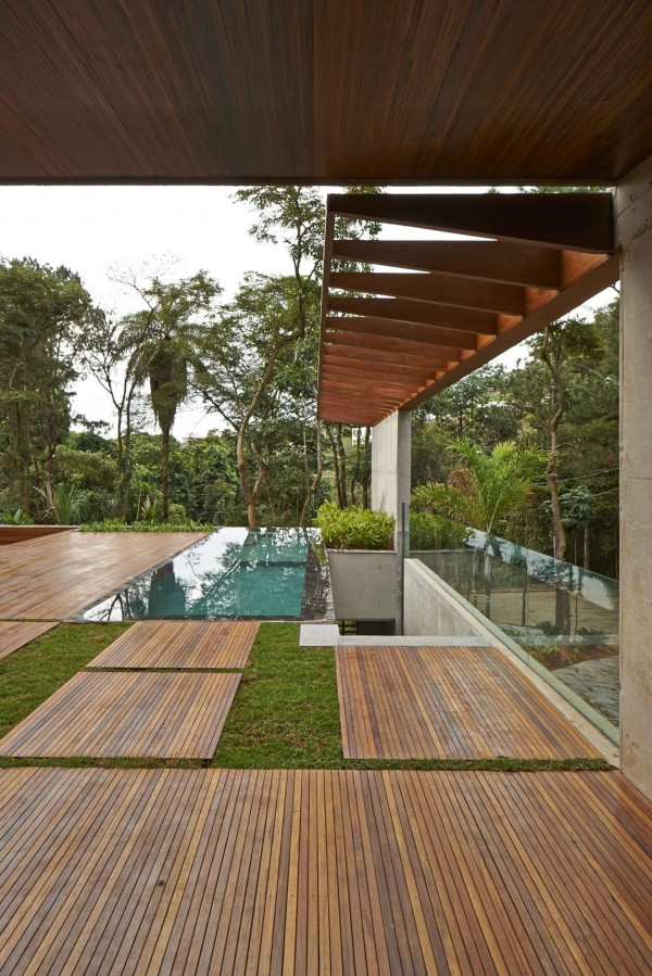 Natural wooden boards in a beautiful deep cherry color are almost made into lilypads between the grass in the backyard.