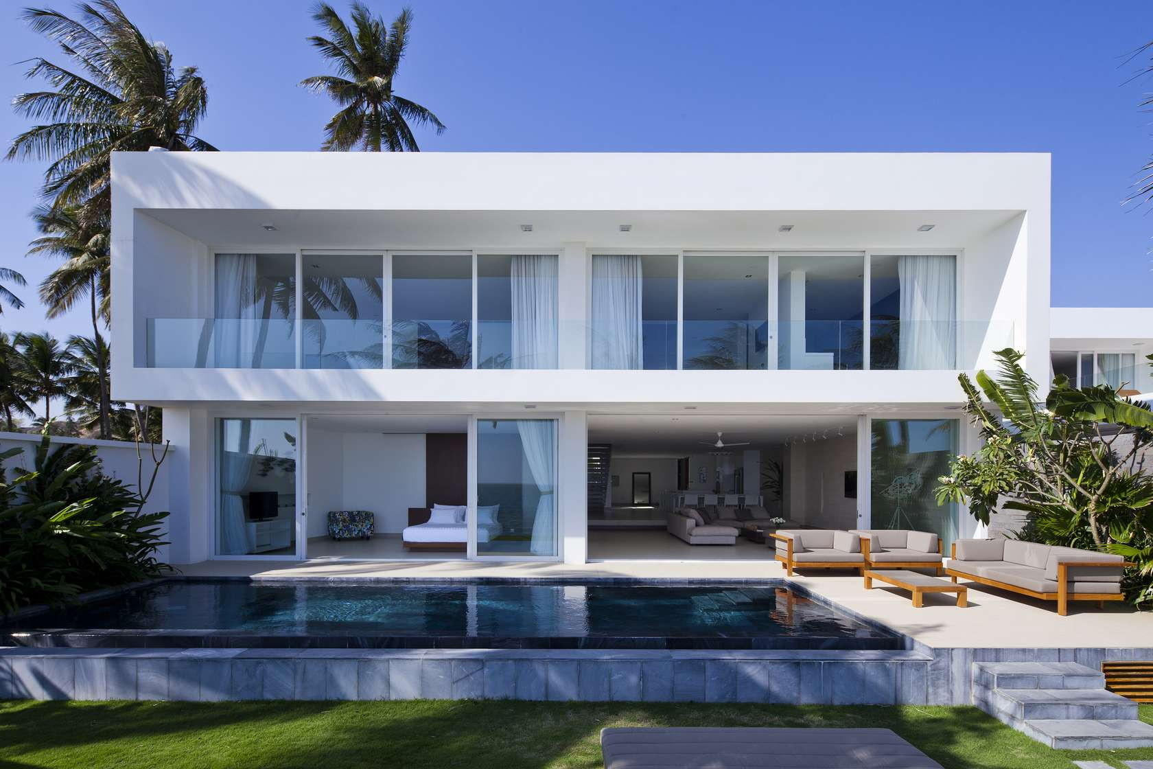 Private beach villas offer spectacular ocean views and for Coastal style house plans