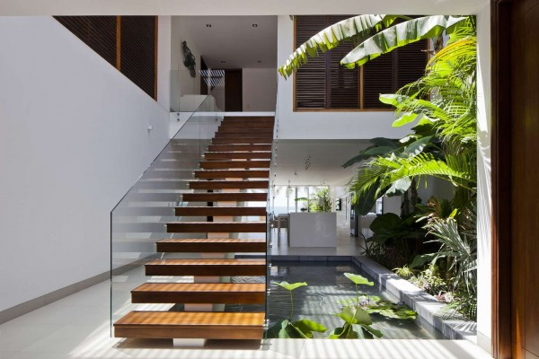 Interior staircases are open to the outdoors, allowing air and people to flow from one level to the next. They are also flanked by private garden areas for a lush, tropical atmosphere.