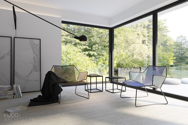 A conversation nook in one corner offers some of the only furniture that is not a muted gray, black, or white. These stylish woven chairs are not jarring, however, because they sit carefully against the vibrant greenery outside the window.