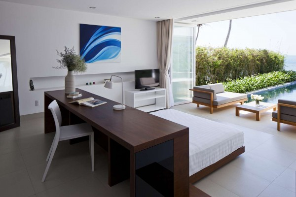 The master bedroom in each villa opens out onto the deck and pool area.