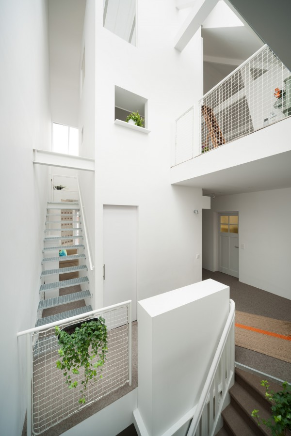 The dark staircase that blocked so much overhead light in the previous design was removed and replaced with a simple metal grated stairway that climbs to the highest level of the home.