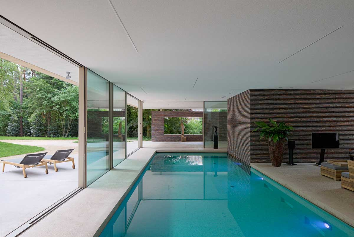 Modern exterior complements its gorgeous natural surroundings for Private indoor swimming pools