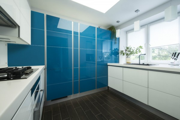 The bright blue kitchen wall is another beautiful burst of brightness, the tone of which carries into the vibrantly colored bedroom as well.