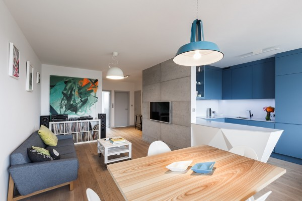The second apartment comes from the architects at Unikat Lab and bring a bit more color, overall, to its design. The main living space, which includes a dining table, sofa, and a small kitchen, uses varying shades of blue to create  harmony while still keeping some separation between the different areas.