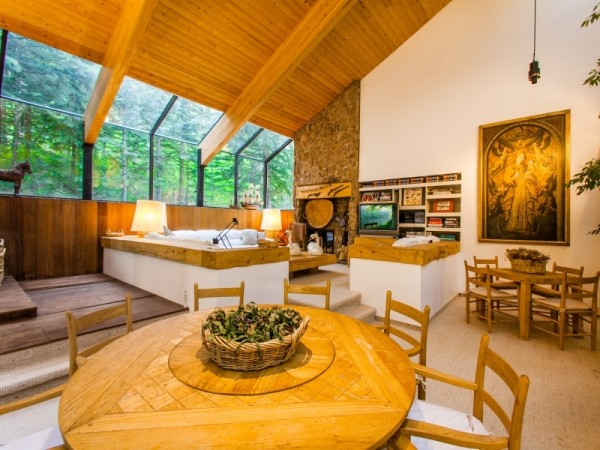 The natural wood throughout the shared living space gives it a timeless rustic feeling while huge windows give majestic views out into the surrounding forests. The architect has even managed to bring the forest indoors with a large planter featuring trees that stretch up to the vaulted ceilings.