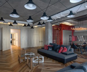 The loft includes an open floor plan and exposed ductwork, both of which are quite common in this style of apartment. In this particular space, the ductwork has been painted white which prevents it from feeling quite so industrial. The gridwork of light fixtures on the ceiling is also a creative addition.