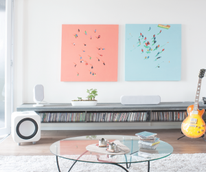 The eye can't help but be drawn to the pretty pastel wall art in this living room. You don't even miss the TV.