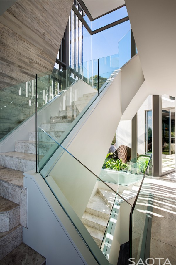 Visitors to the home are sure to be instantly impressed. A set of gorgeous concrete stairs leads up to a massive foyer where they encounter a custom water feature as well as slivers of the view that lays beyond the entrance.