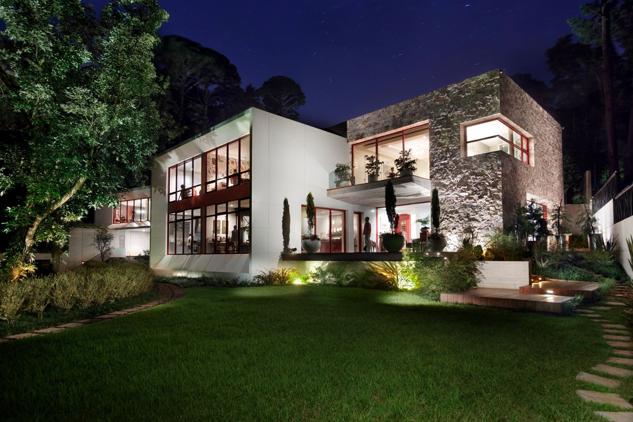 Lush Landscaping - A warm stone exterior houses an intimate residence