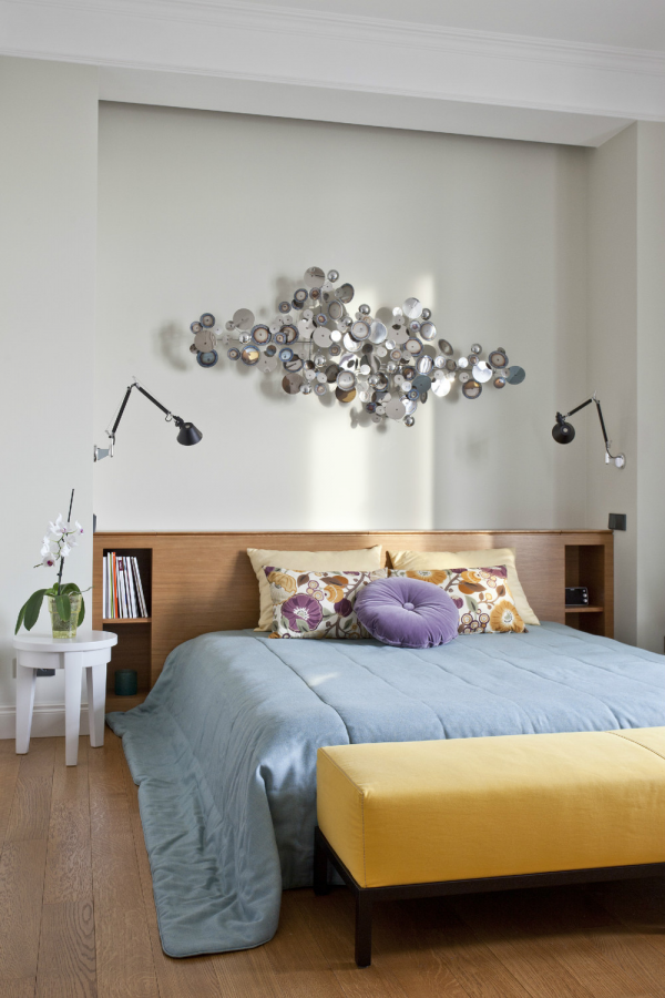 A funky silver sculpture brings some edgy creativity into this bedroom that is otherwise quite standard.