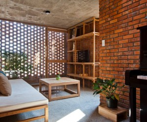For a house made entirely of brick, the interior is surprisingly warm and welcoming with sunlight streaming in from overhead openings and the airy exterior. The use of wood as a whole is kept to a minimum, with a few pieces of custom furniture and a small cooking area with wood cabinetry.