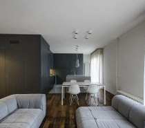 """The main living area is the """"day"""" area of the apartment, proving space for entertaining, relaxing, cooking, and eating. The design here is the height of simplicity, even going so far as to avoid hanging anything on the walls. Instead, art is propped up on the ground and the television is hidden in a custom wood cabinet. The sofas are arranged around the entrance to the home, making the flow from visitor to guest seamless."""