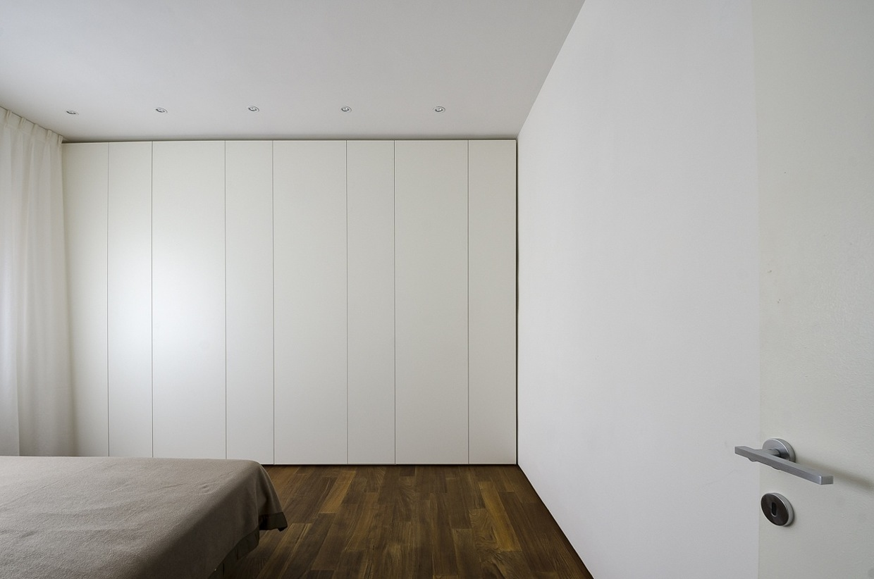 White Closet Doors - Italian apartment renovation brings open space to 1960s home