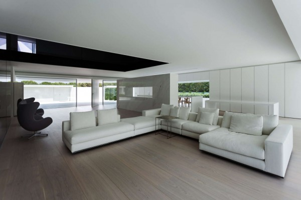 Inside the home, everything feels open with air and light flowing from one side of the house to the other easily. Minimal furniture serves to open up the space even further on both levels. Colors are kept to a minimum as well, with shades of white and gray making up most of the home. From every angle, occupants can look out onto the garden or surrounding greenery, giving the home a feeling of being both at one with and entirely removed from its natural surroundings.