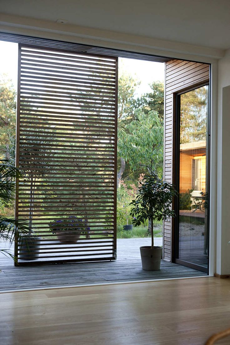 Wood slats add texture and warmth to these homes for Wood patio privacy screens