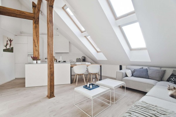 The attic itself is not enormous, but the vertical space meant there could be enough room for a comfortable home as long as things were arranged creatively. The architects used the vaulted, slanted ceilings to create a mezzanine which in turn created the effect of a two story home, with a bedrooms tucked upstairs and an open living area below.