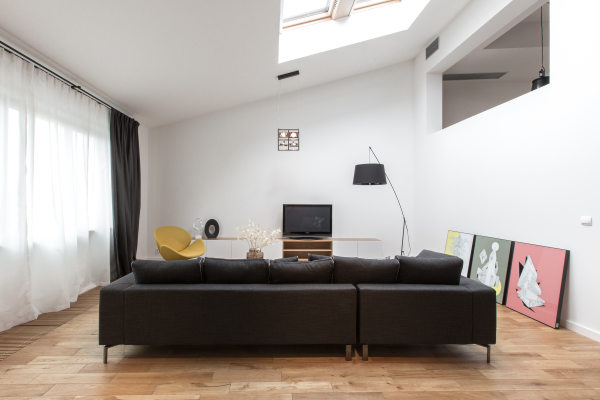 A top floor living room lends itself to a gently sloping ceiling and stunning skylight.