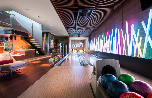 "The basement bowling alley has all the trappings of a teenage retreat, but with a modern pool table and custom neon lighting from designer David Singer, it can easily take a more adult turn. To reach the bowling alley, guests can take the hidden interior elevator, labeled with buttons ""Sleep,"" ""Eat,"" and ""Play."" Also downstairs is a private screening room and fully stocked bar."