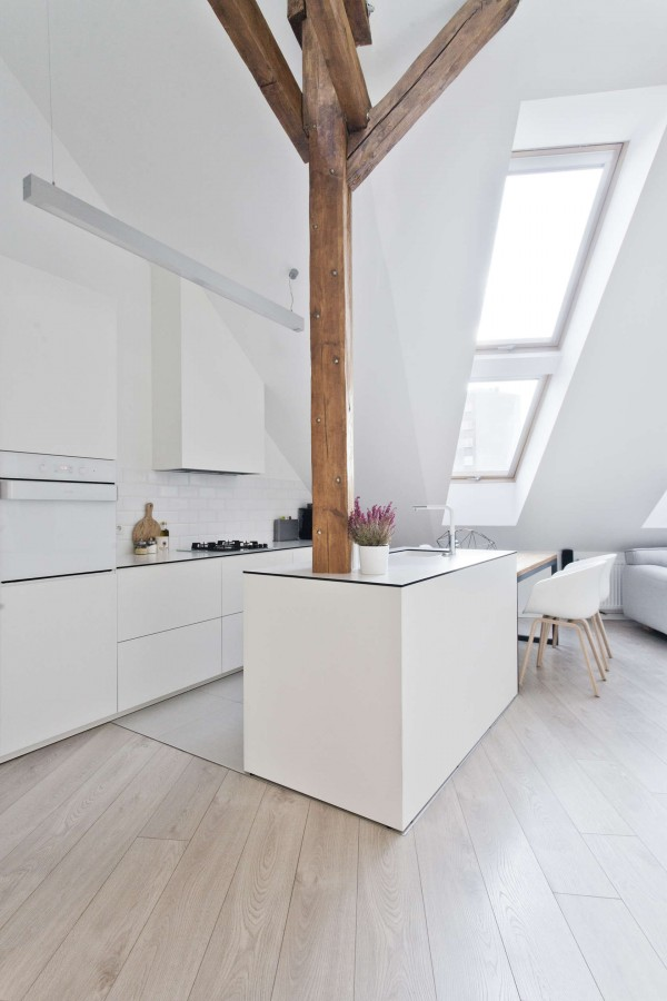 The white color of the space, blending easily with the light colored wood floors, make the home feel bigger but the contrasting natural wood supports give it a unique twist. Most of the furniture is kept quite simple, in both color and shape utilizing the same wood and white palette. A few of the pieces in the home are actually made from wood that was salvaged from the demolition of the original attic space.