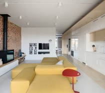 The main living area and open kitchen are a welcoming introduction to the home. A stunning butter yellow sofa is just about as cozy looking as any couch with lots of space to stretch out for a long nap. The bright pop of color certainly stands out but it lives in a subdued hue that isn't garish. And of course, regular visitors to this blog know how timeless and stylish an exposed brick accent wall can be.