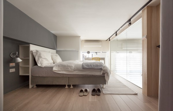 The bedroom is soothing with tones of gray and tan. Soft textures of wood, wall, and linens make the space feel welcoming.