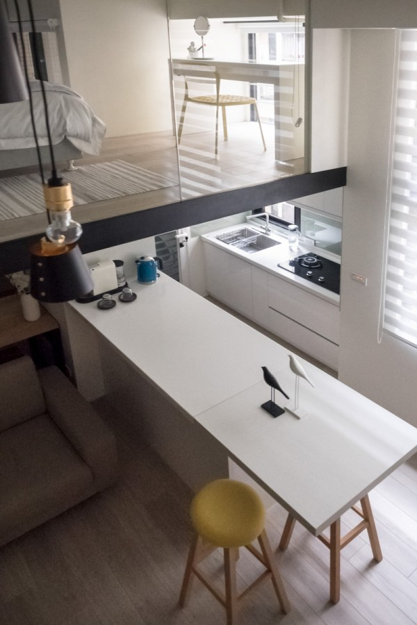 A vanity table placed at the corner of the sleeping area allows the light to flow in for makeup application at its best.