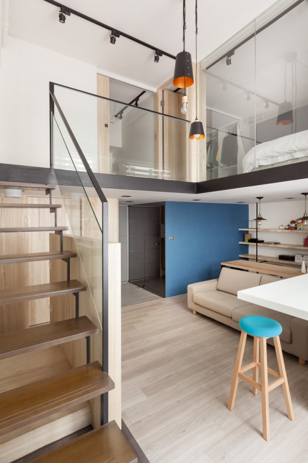 The steps leading up to the second floor loft are works of art in their own right. Wood and black metal cut through the white of the walls and are complemented by the glass sheets alongside the railings. A whimsical yet industrial collection of pendant lights soften the overall look.