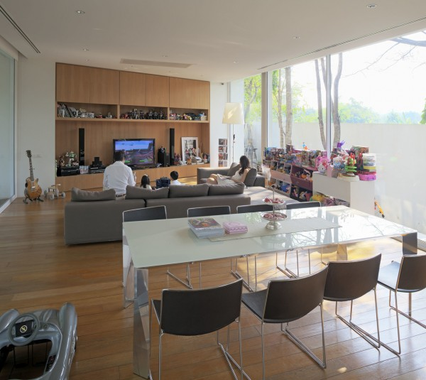 The first space as the floor-to-ceiling windows and low, clean profile that is indicative of a stylish modern home. The wood elements in this house are particularly notable with rich lacquered wood covering floors and walls. The outdoor carport is also quite stylish, emphasizing the fluid life of a Thai family that merges the indoor and outdoor easily and almost without thought.