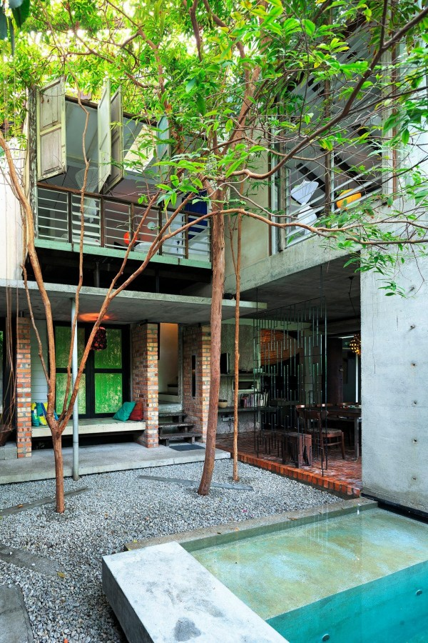 The second home is taller, standing two stories, and utilizes surrounding greenery to great effect. The vibrant leaves on trees that burst forth through the pool deck stand in sharp and beautiful contrast with the concrete exterior. A second level balcony looks out over the pool and courtyard area while glass doors slide open for plenty of ventilation, even during the steamy summers.