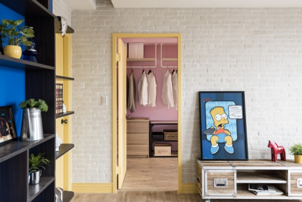 The bedroom carries the eclectic theme with a bit more color, including lemonade yellow, pretty pink and some fun patterns on the bed linens. The warm and sunny space is perfectly welcoming, not falling prey to a colder industrial design. The final touch for storage is a spacious walk-in closet in the aforementioned lovely petal pink tones. Who could imagine a more cheerful place to get dressed.