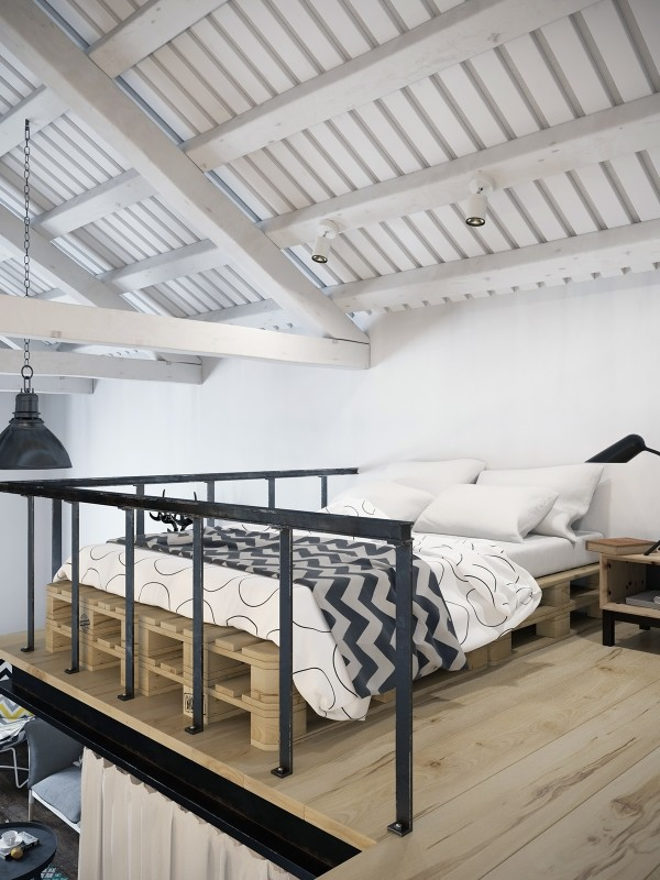 The lofted bed area is ultra cozy and certainly simple. The bed itself is actually made from wooden pallets while a chevron stripe duvet brings some design elements from downstairs up into the bedroom for a unifying feel. The loft is also placed far enough below the pitched ceiling that it doesn't feel cramped, which is often an issues for spaces like this.