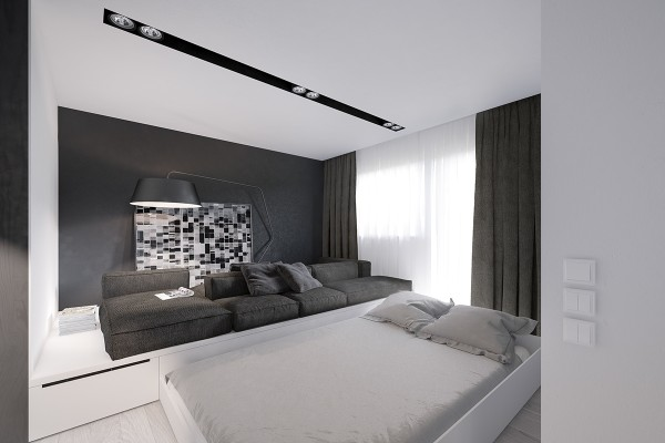 A large sofa in the living room exists atop a platform, underneath which is hidden a double bed that slides out at night. The living room also includes a workspace, nestled amid the storage areas in the walls.