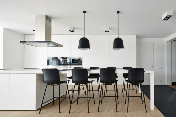 Thin breakfast stools advance the minimalistic aesthetic by placing void over form in a kitchen filled with substantial surfaces in white. This clever reversal seems to derive visual weight from contrast rather than form.
