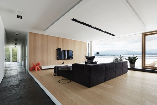 A pleasantly minimalistic take on luxury design, this home from Boom Architects uses simple forms and casual colors yet weaves them into a narrative that immediately catches a viewer's attention. The classic combination of black, white, and light glossy wood yields itself to a surprising pop of surprising color courtesy of the iconic Magis Puppy.