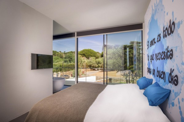 In this bedroom, bright cerulean matches the pool and Mediterranean waters outside. Around the corner, a modern soak tub enjoys an uninterrupted view of the hills.